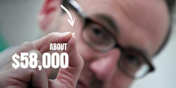 Adam Bandt holds a grain of rice. Caption, overlaid: About $58,000